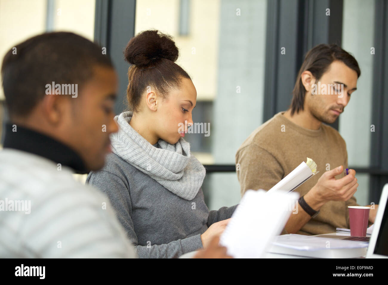 Young african american woman reading notes with classmates studying around in university library. Students preparing for exam. - Stock Image