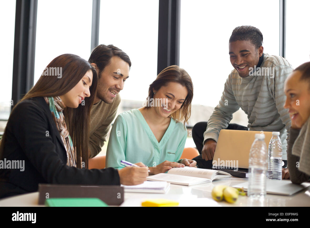 Group of multiracial young students studying together at a table. Mixed race people doing group study. - Stock Image