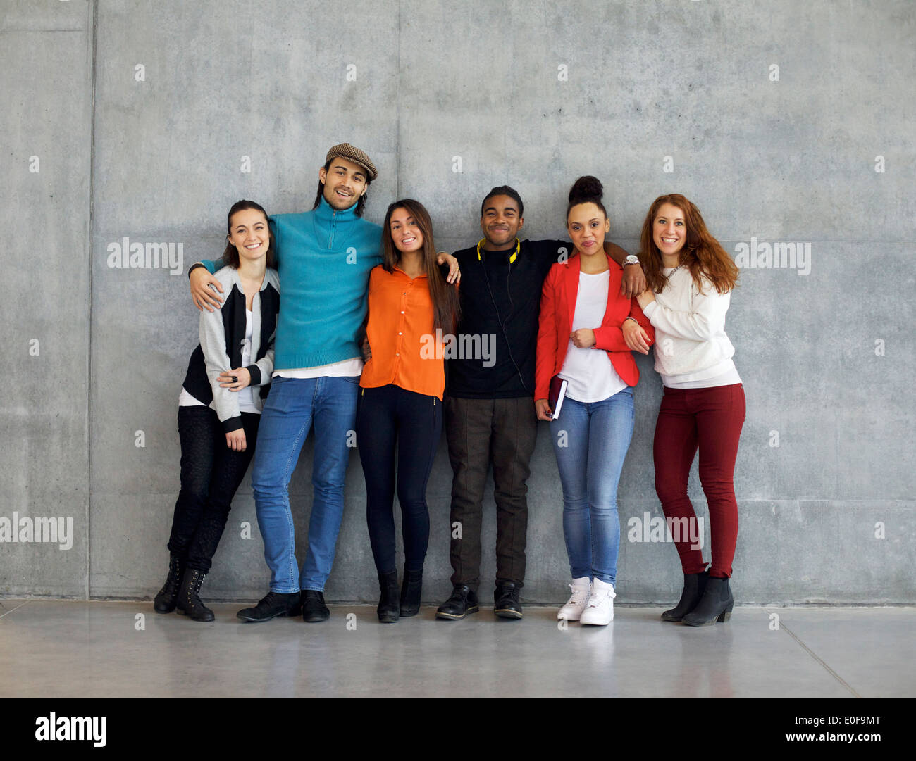 Multiethnic group of happy young university students on campus. Mixed race young people standing together against wall. - Stock Image