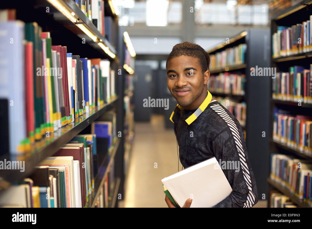 Image of happy young man standing by bookshelf in library. African american student in public library holding books. - Stock Image