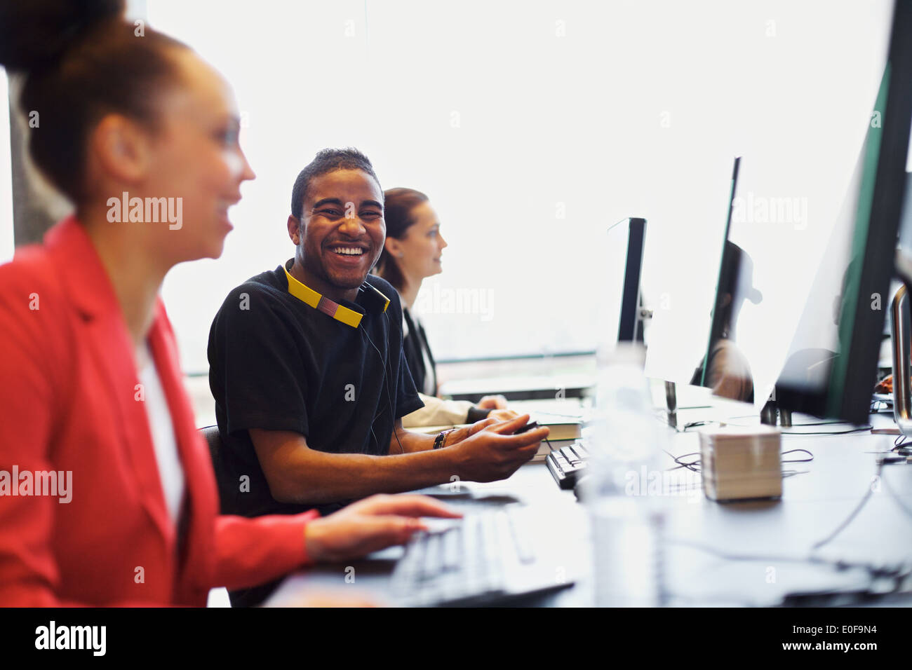 Young afro american man looking at camera smiling while working on computer in modern classroom. Young students studying. - Stock Image
