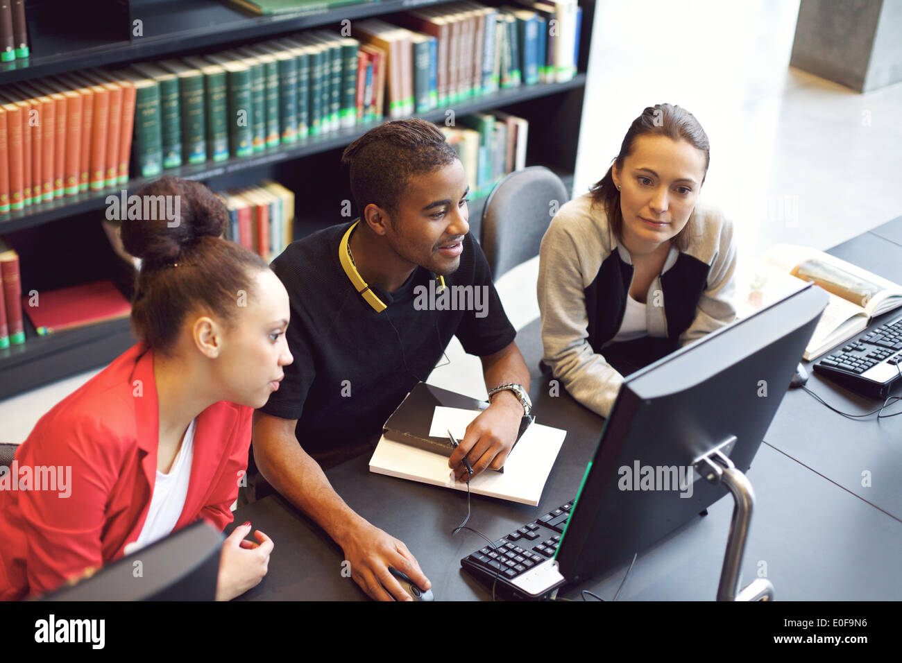Three young university students studying in library using computer. Young people sitting at table with books finding information - Stock Image