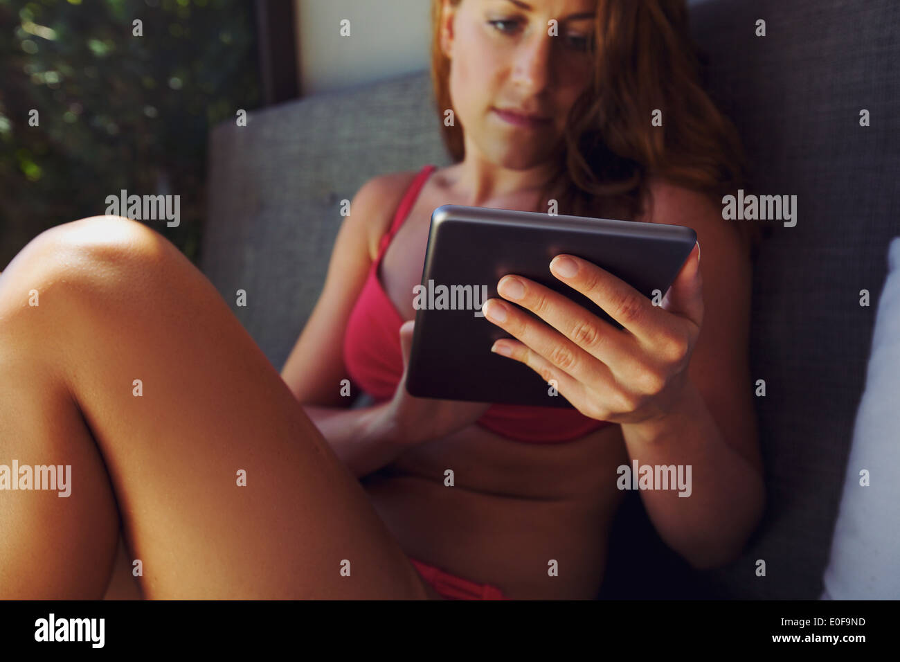 Closeup image of young female model using digital tablet. Young caucasian woman in bikini sitting on couch using tablet computer - Stock Image