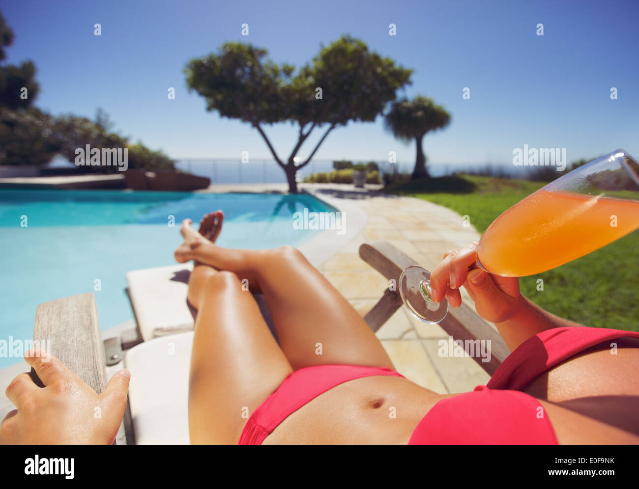 Female model in red bikini lying on a deck chair drinking a juice on a sunny day by swimming pool. Young woman sunbathing. - Stock Image