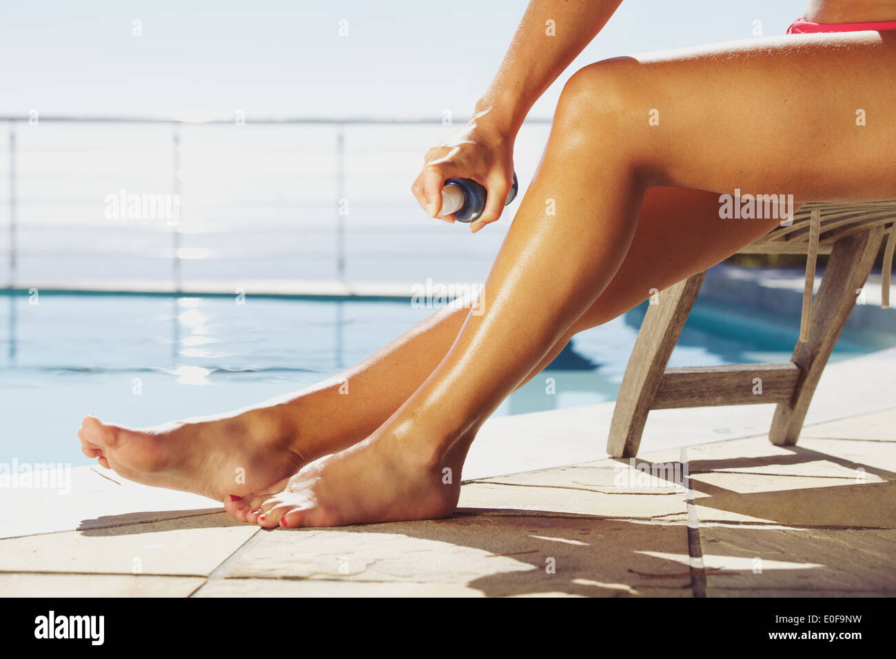 Woman applying suntan spray onto her legs. Female sitting on recliner chair by the swimming pool sunbathing. - Stock Image