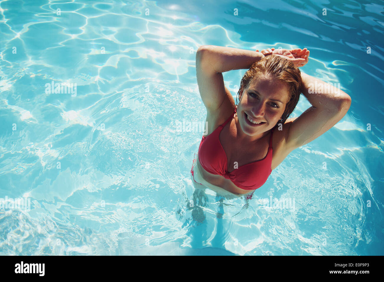 Top view of attractive young lady in a swimming pool. Happy young caucasian female model in swimwear looking at Stock Photo