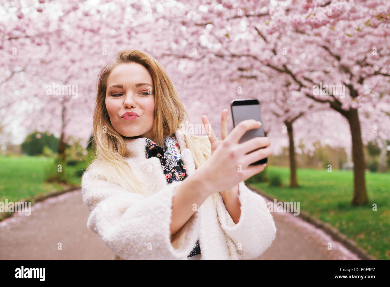 Cute young woman gesturing peace sign while taking her picture with mobile phone. Caucasian female model at spring blossom park - Stock Image