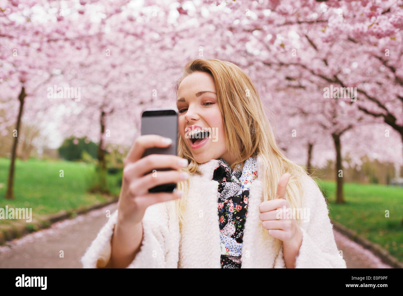 Cheerful young woman talking her picture with her cell phone and gesturing thumbs up sign. Caucasian female model posing. - Stock Image