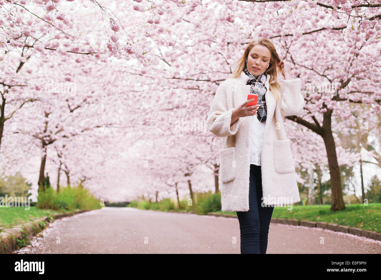 Young lady at spring park listening music from her mobile phone. Relaxed woman taking a walk at spring blossom garden. - Stock Image