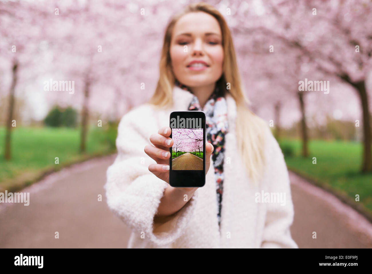Young woman showing a photograph on her smart phone at you. Female at spring park displaying images on her mobile phone. - Stock Image