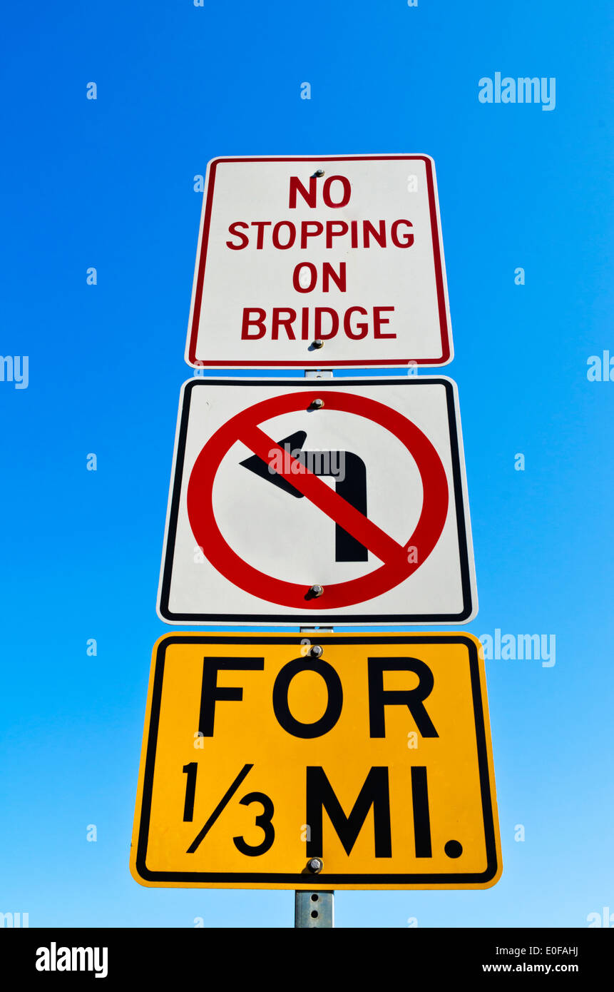 No Stopping on Bridge No Left Turn sign against a blue sky. - Stock Image