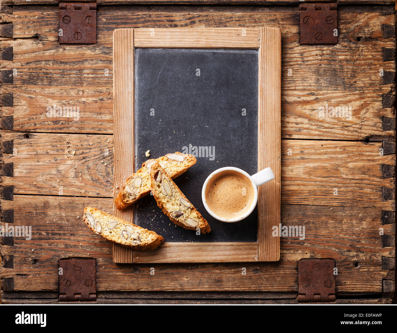Coffee cup and biscotti on vintage slate chalk board - Stock Image
