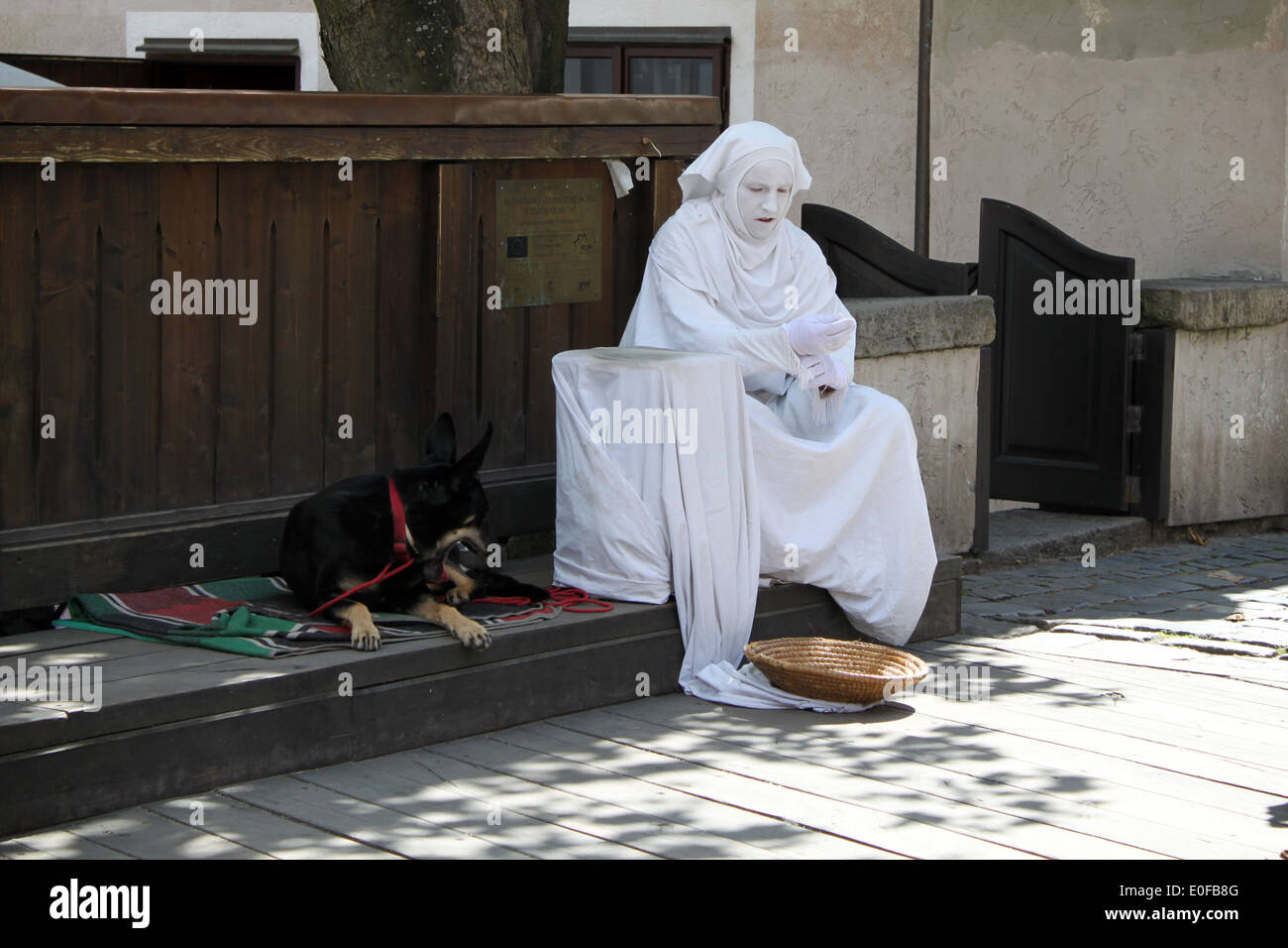 A living-statue street performer and his dog resting between acts. - Stock Image