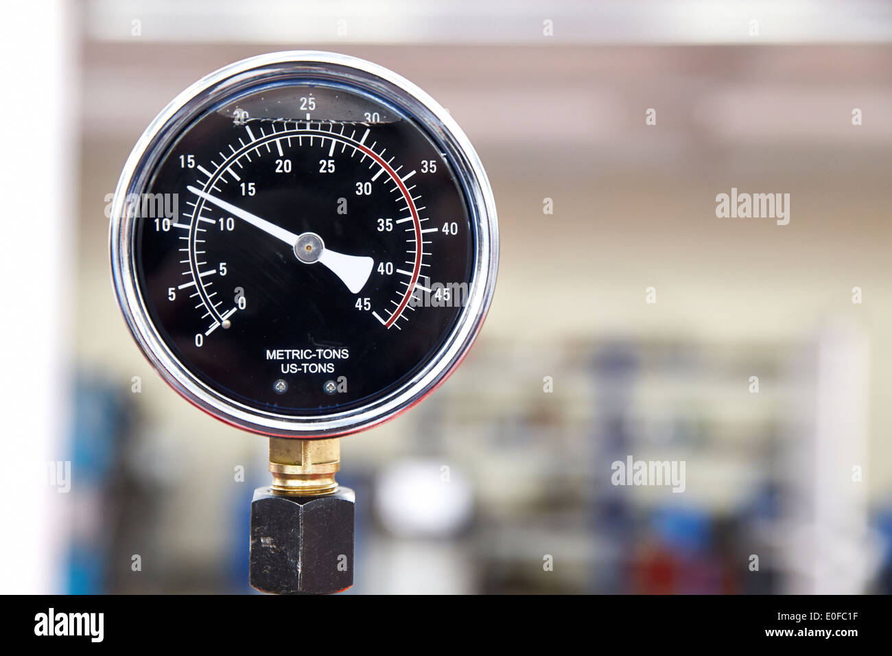 A pressure dial, sensor or monitor on a factory floor in a manufacturing plant. - Stock Image