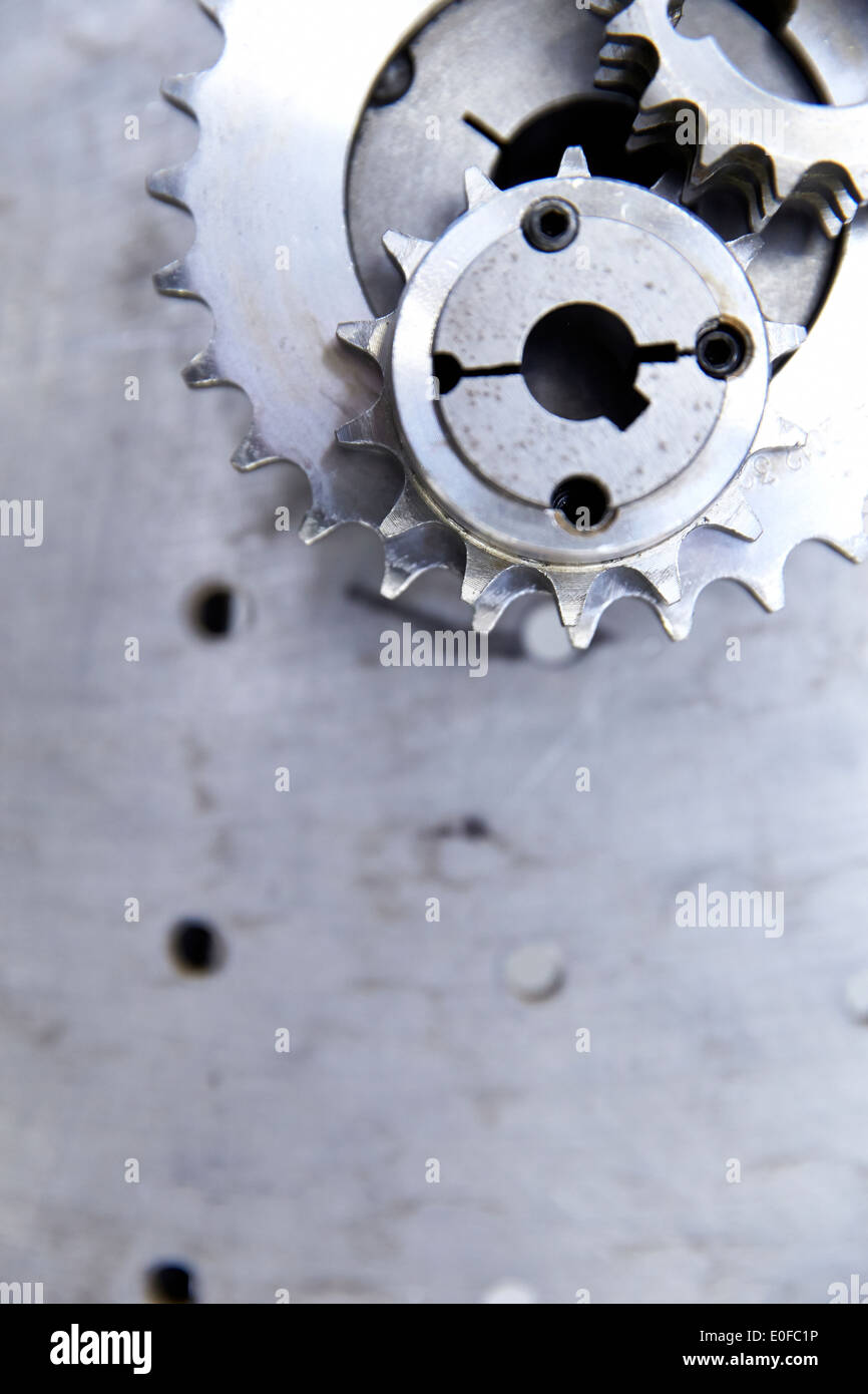 Cogs and gears on a metal work bench in a manufacturing factory - Stock Image