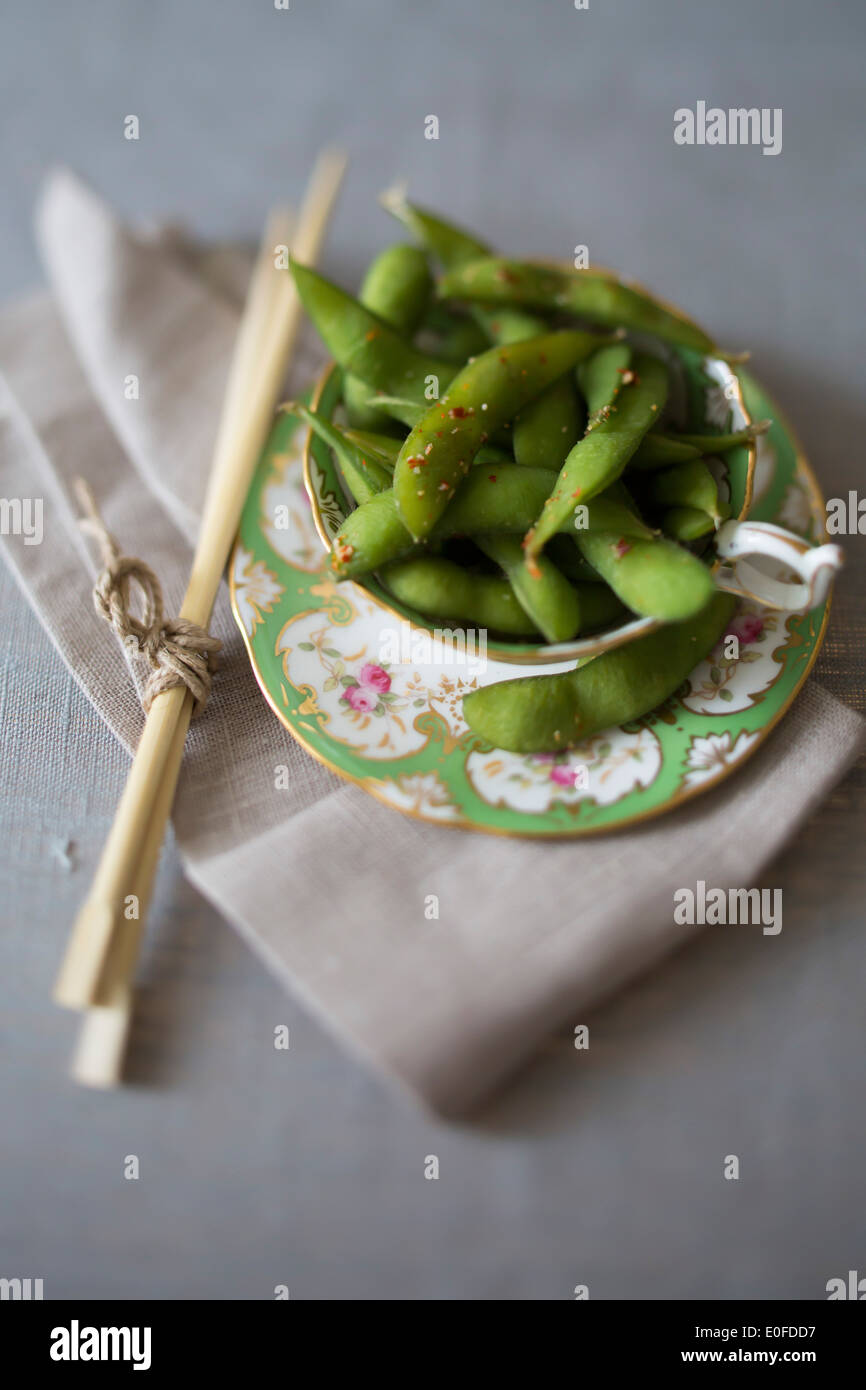 Tea cup of chilli edamame with chop sticks - Stock Image