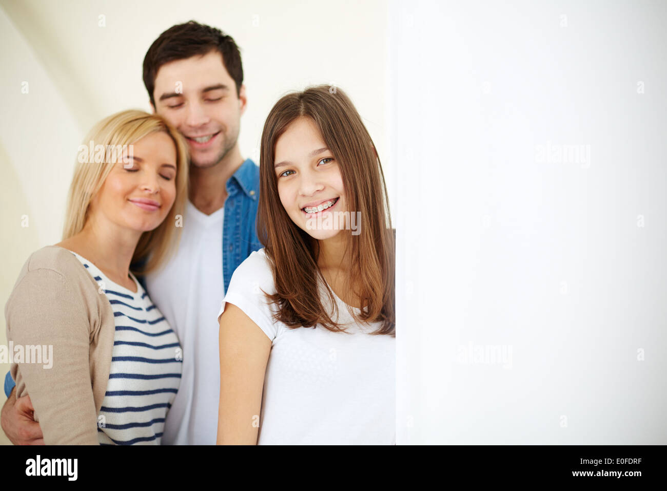Portrait of happy family of three in isolation - Stock Image
