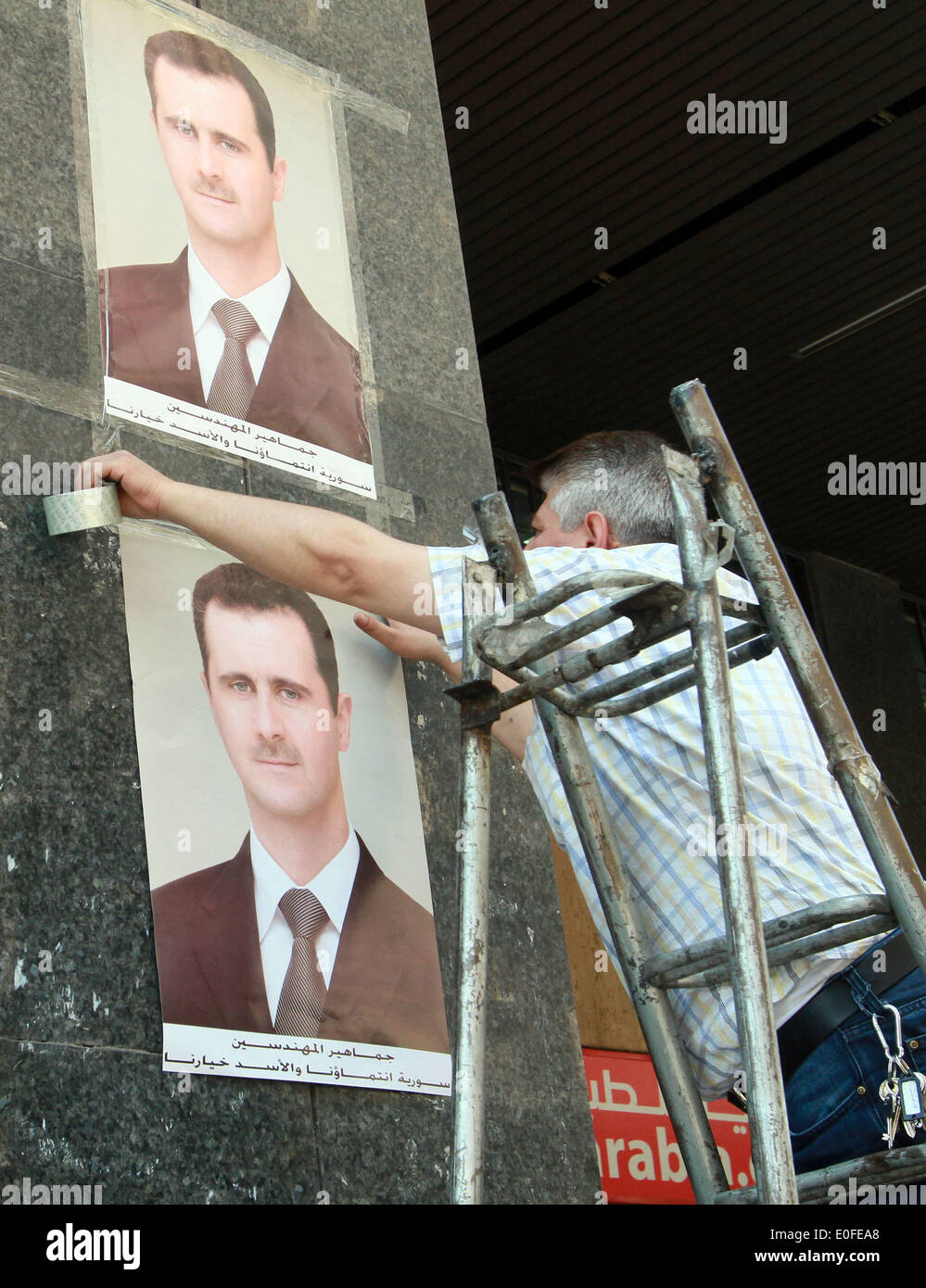 Damascus, Syria. 12th May, 2014. A worker puts up election posters in Damascus, Syria, May 12, 2014. A day earlier, Stock Photo
