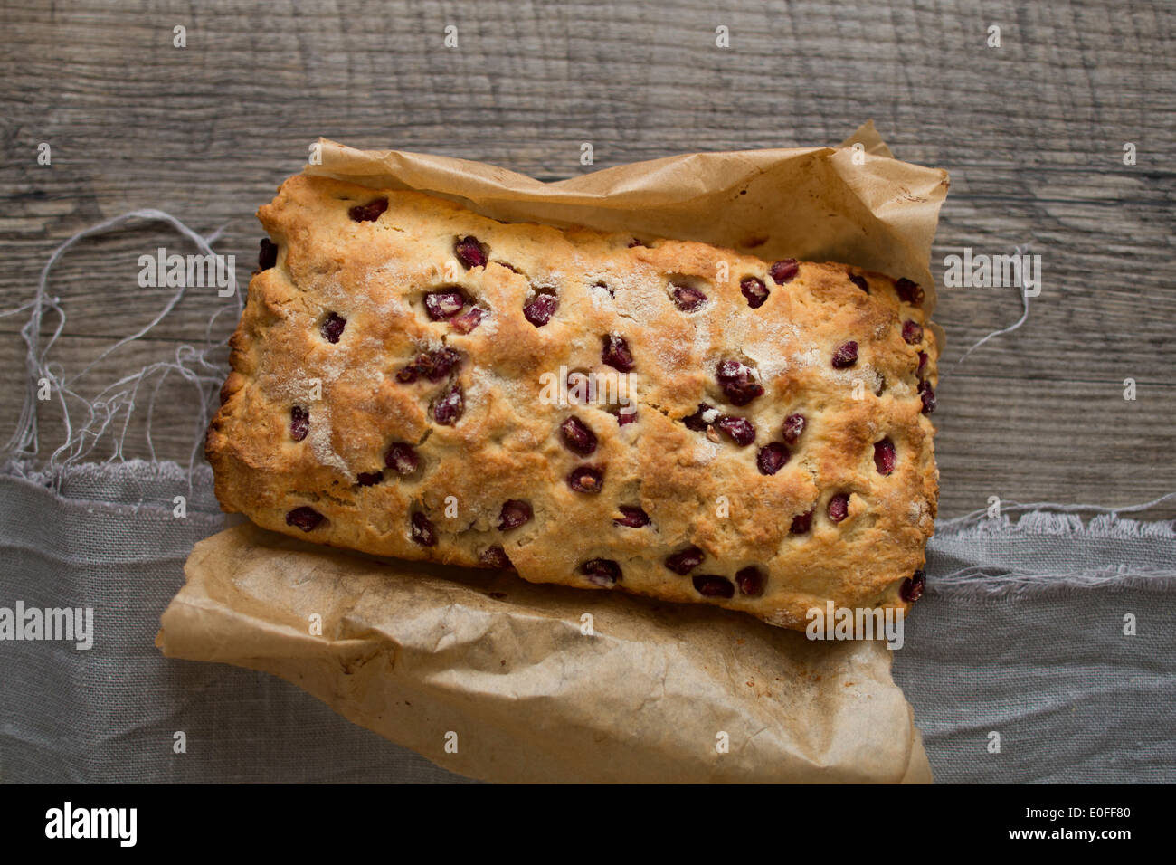 Pomegranate Scone Loaf whole on parchment paper - Stock Image