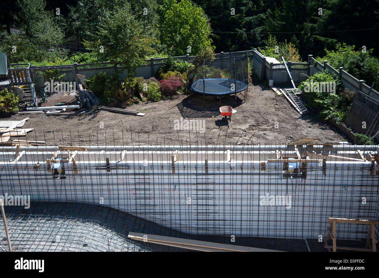 Backyard pool being built with rebar lining installed - Stock Image