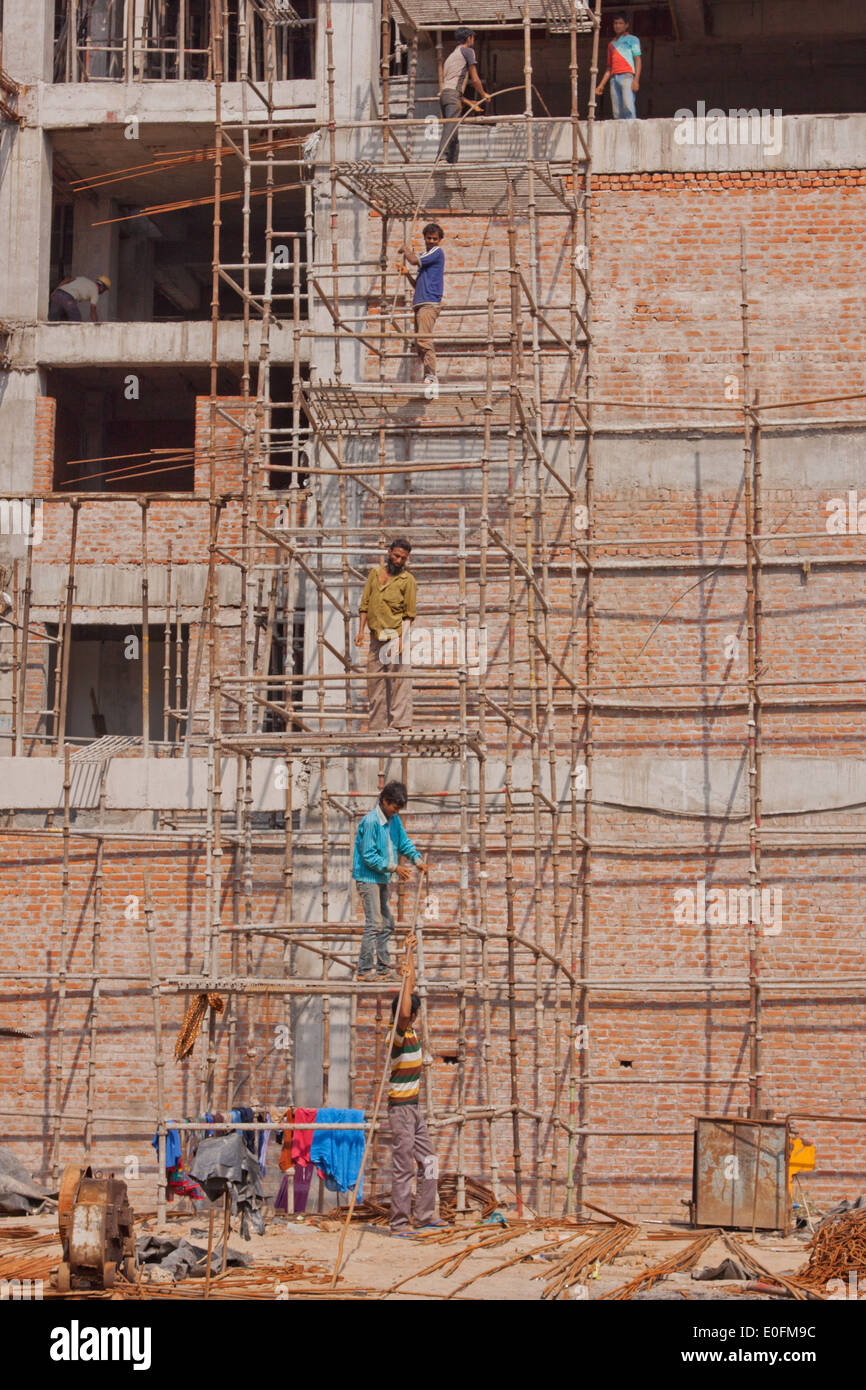Workers form a chain to assemble additional wooden scaffolding at the top of a building under construction in Delhi, India - Stock Image
