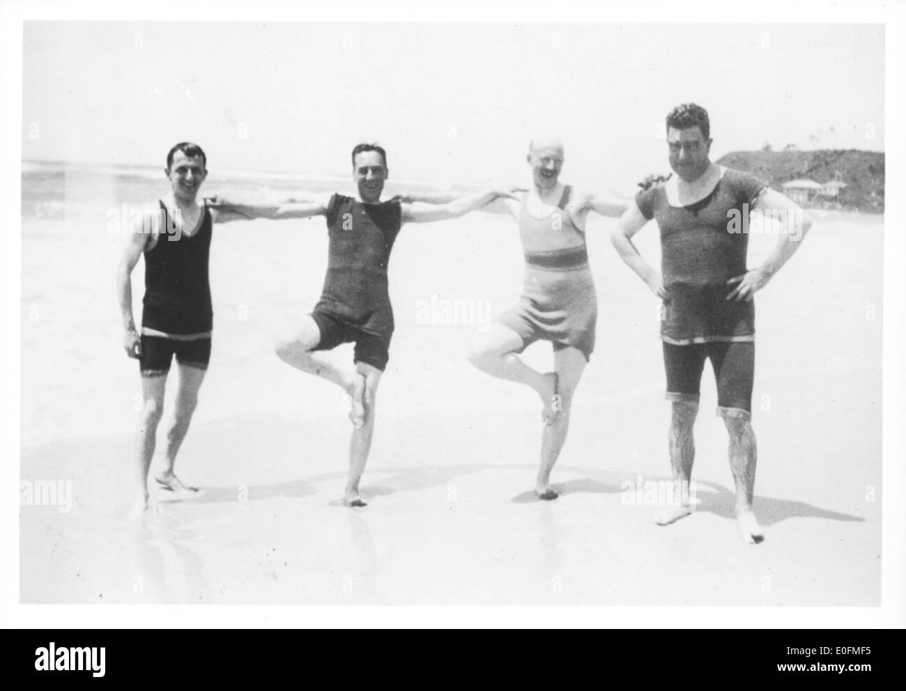 Portrait Of Four Men In Swimming Costumes On A Beach During The