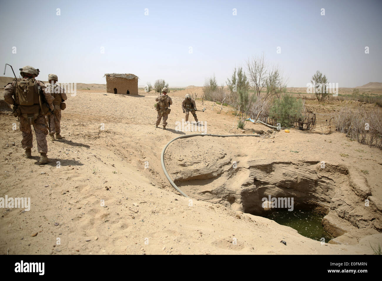 US Marines with the Bravo Company assault force speaks patrol on the outskirts of a village during a counter insurgency Stock Photo