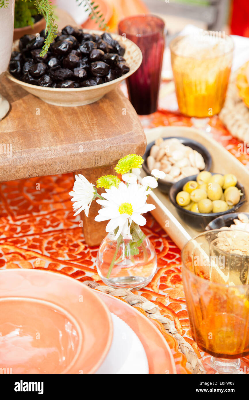 Hors Doeuvres In Moroccan Themed Table Setting Olives And Nuts With Daisy Floral Arrangement Orange Glasses Bowls