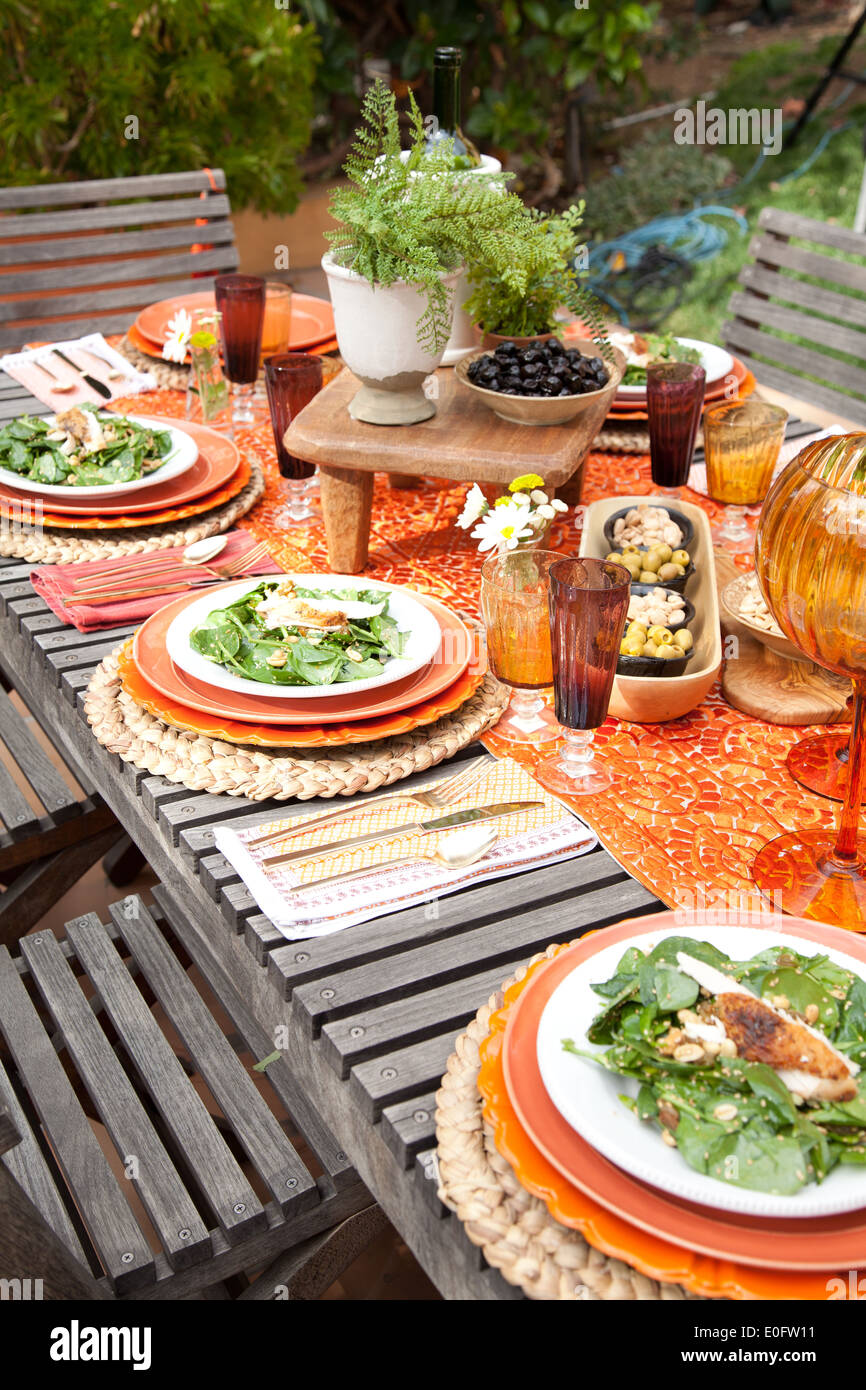 Table setting for spring garden party with spinach on orange plates and orange table runner on wood table with wood chairs. & Table setting for spring garden party with spinach on orange plates ...