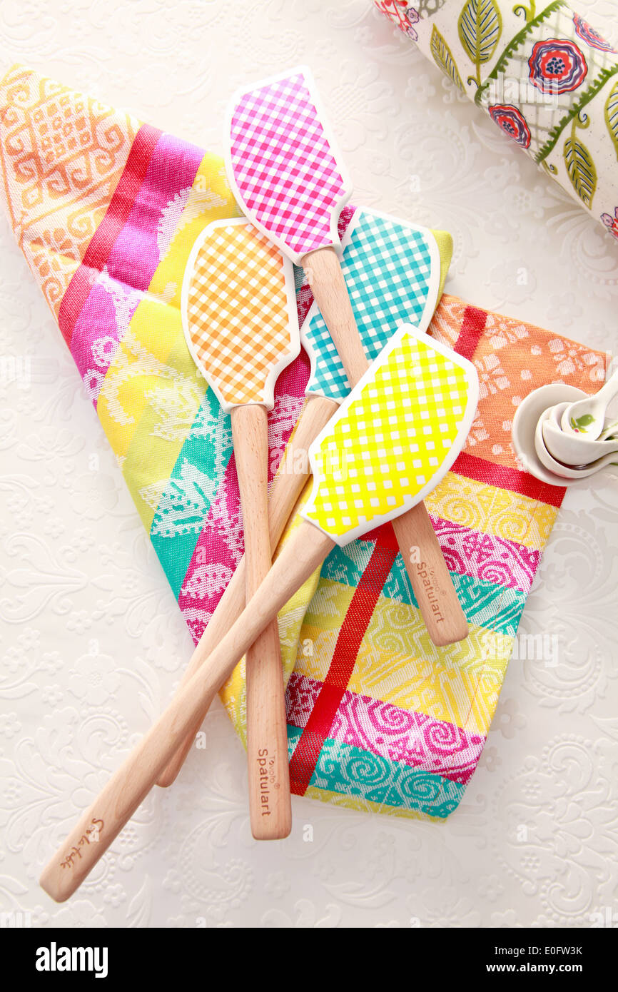 Gingham pattern spatula on graphic napkin with floral rolling pin - Stock Image