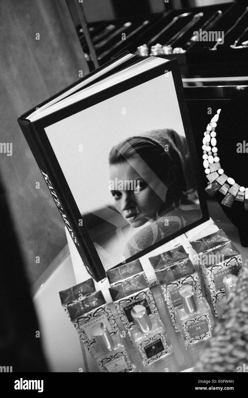 Black & white closeup of jewelry, perfume, and Kate Moss book in an upscale boutique. - Stock Image