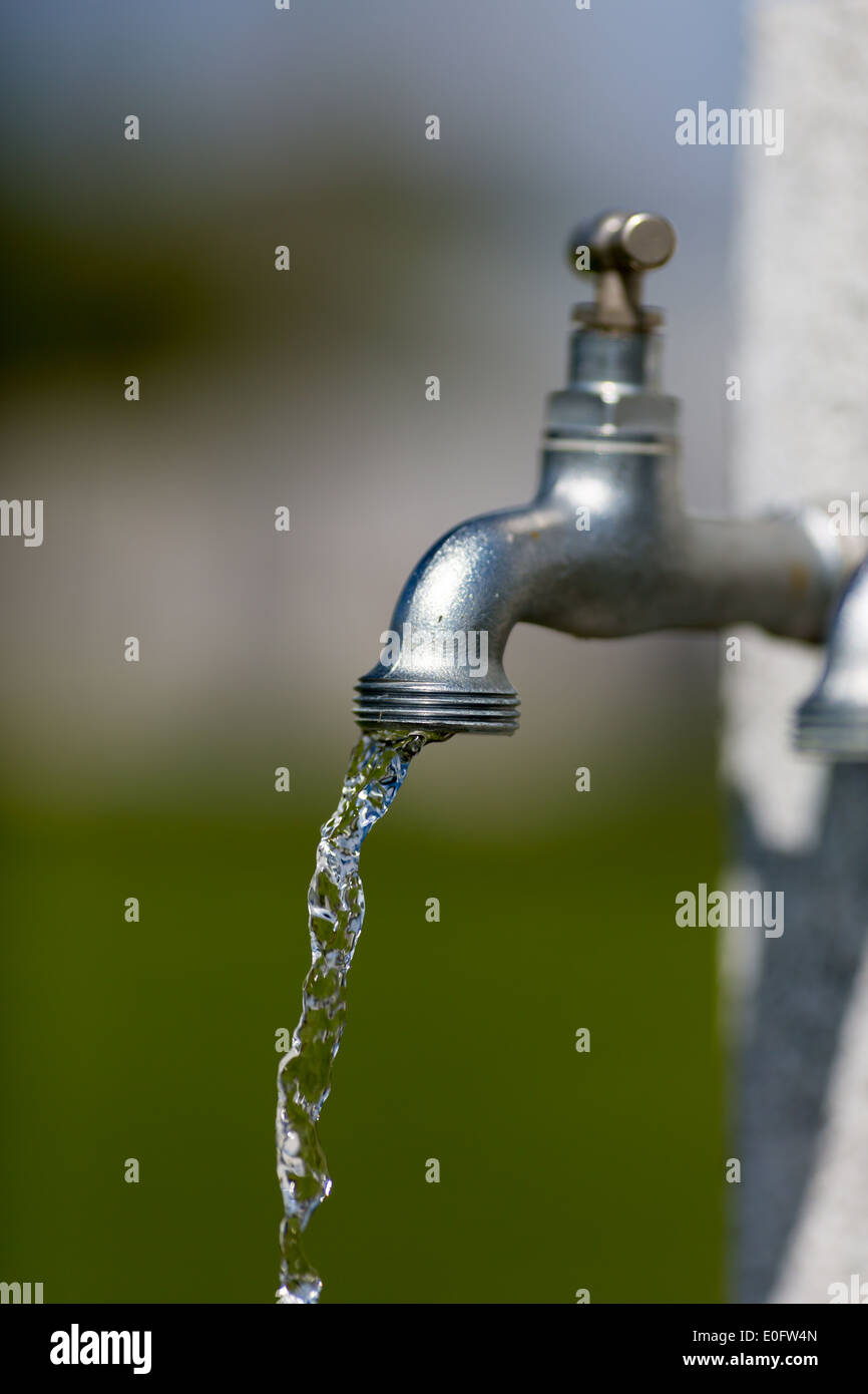 Water flowing from outdoors water tap on a sunny day. - Stock Image
