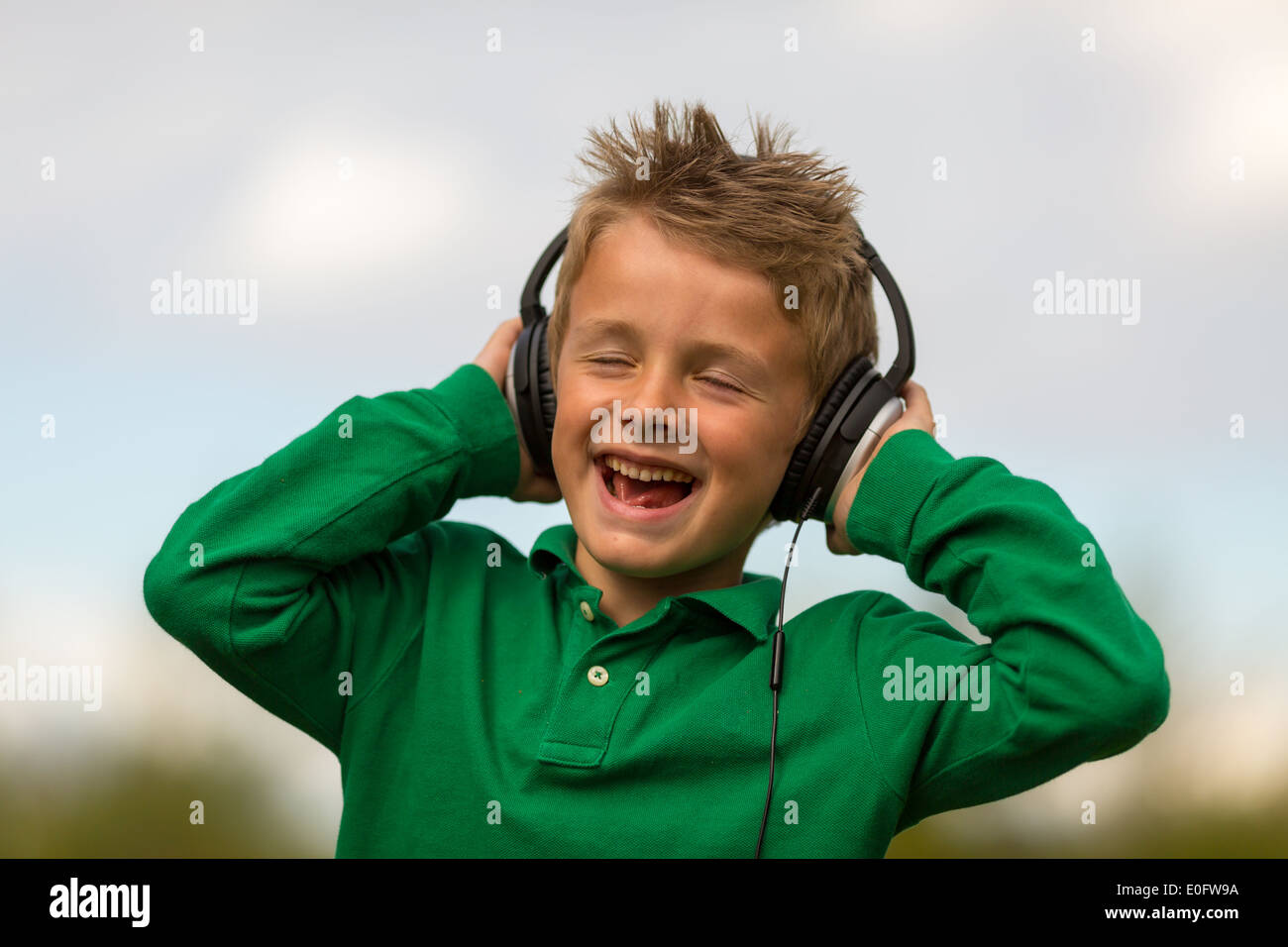Boy listening to music and singing along. Trademarks have been removed. - Stock Image