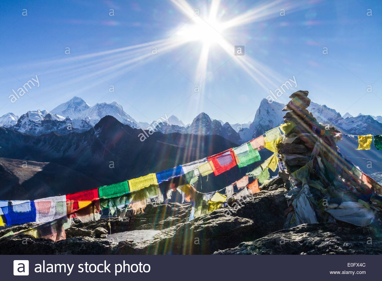The Sun Hovers Above A Rock Cairn Adorned With Prayer Flags With Mount Everest In The Background, Gokyo Ri, Himalayas, Nepal - Stock Image