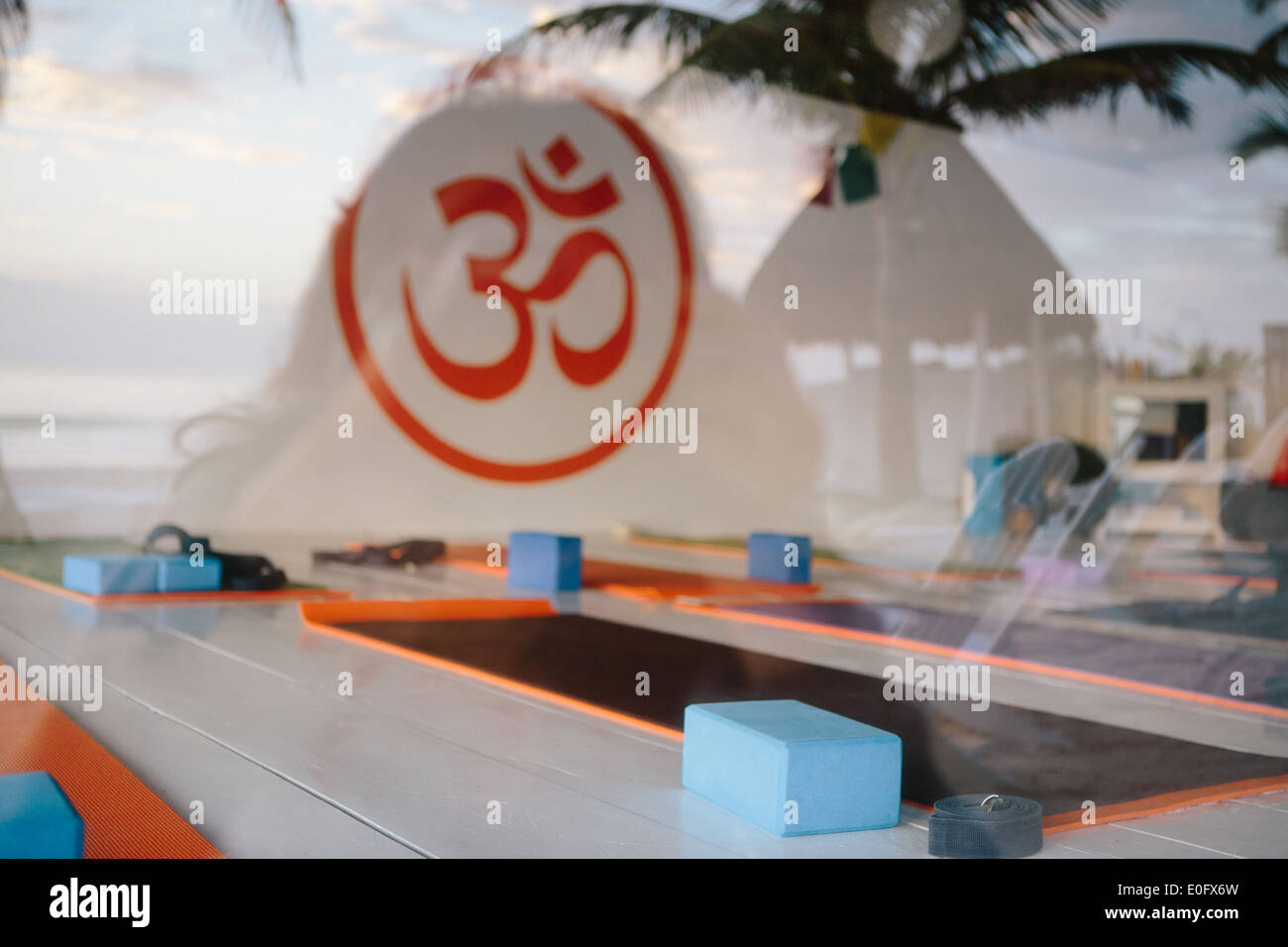 View of empty yoga studio with yoga mats and yoga blocks with Om symbol painted in orange on the wall with palm tree reflections - Stock Image