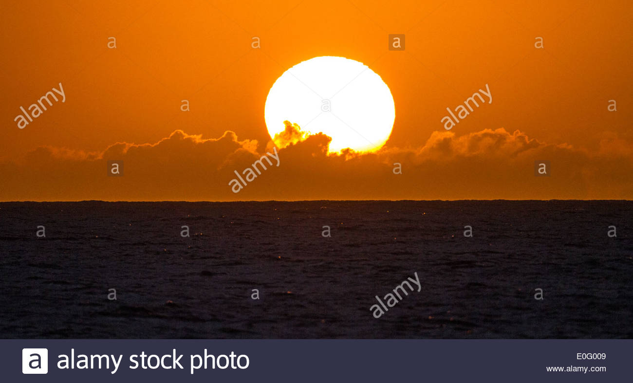 The sun sets over a small bank of clouds above the Pacific Ocean off the shore of Hawaii - Stock Image