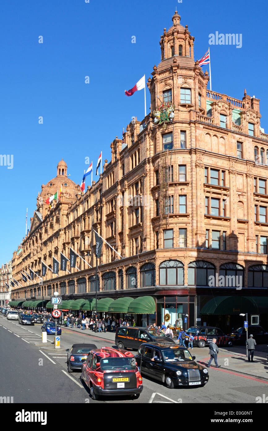Brompton Road and Harrods luxury department store listed building in Knightsbridge on a blue sky day in West London street England UK - Stock Image