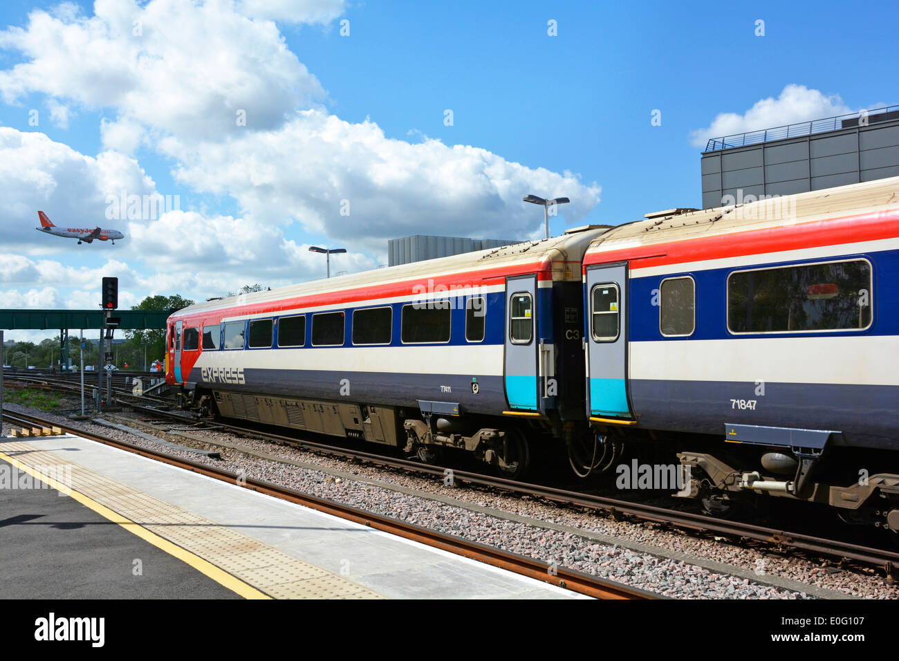 Gatwick Express train at Gatwick Airport station with Easy Jet plane landing - Stock Image