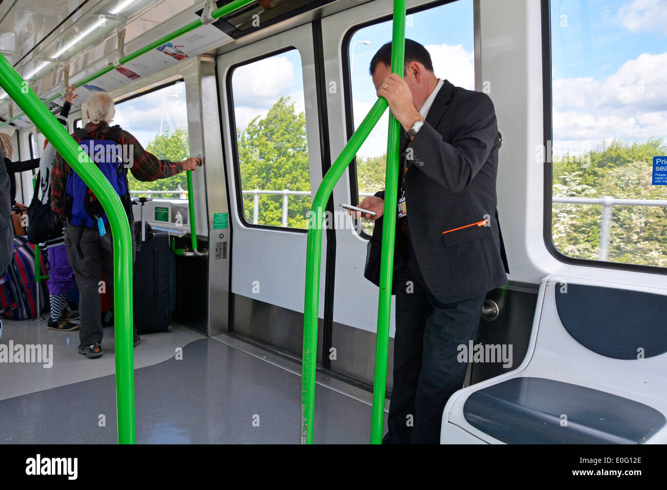 Passengers on Gatwick Airport people mover shuttle train interior joining North & South terminals Crawley West Sussex England UK - Stock Image