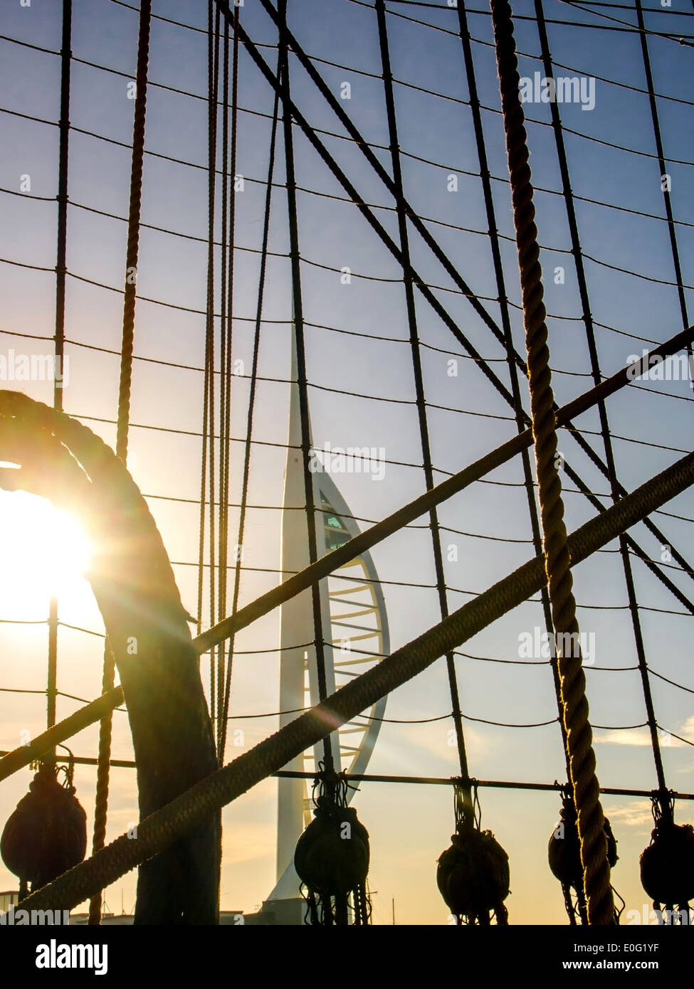 The Spinnaker tower in the morning, viewed through the rigging, blocks and tackles of HMS Warrior, Portsmouth Historic Dockyard - Stock Image