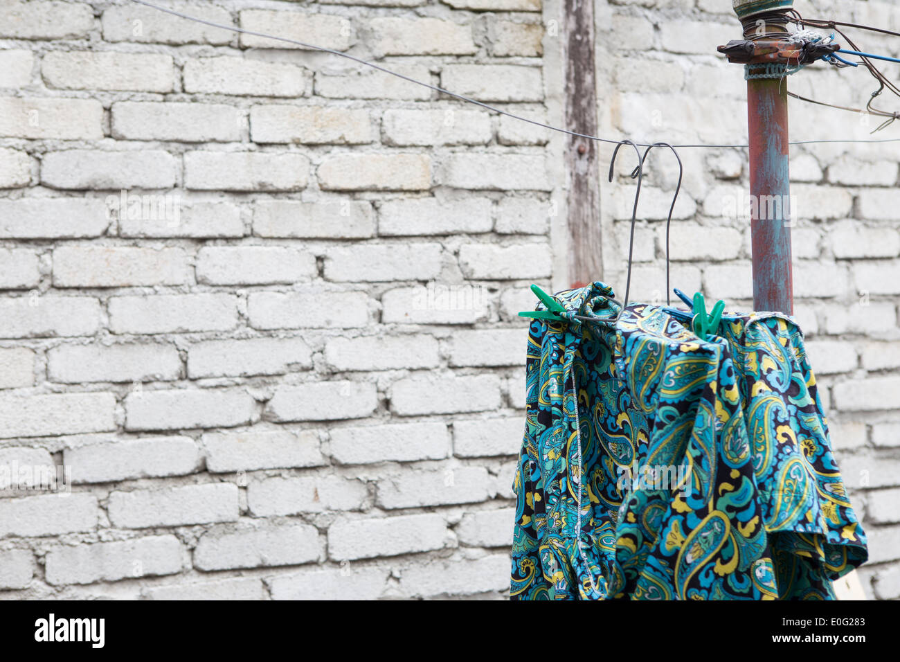 Blue and green patterned shirt on a wire clothesline in front of a ...