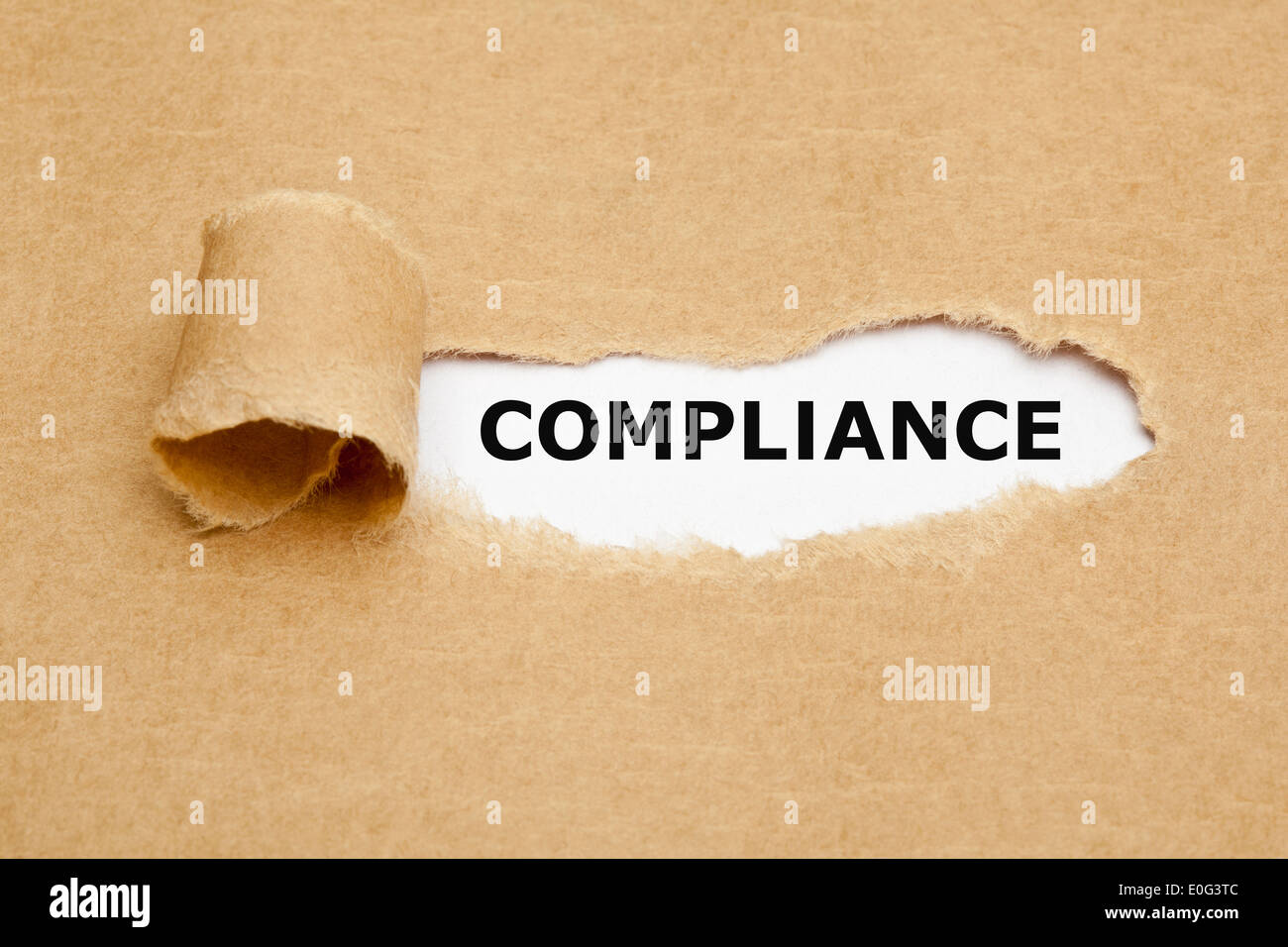 The word Compliance appearing behind torn brown paper. - Stock Image