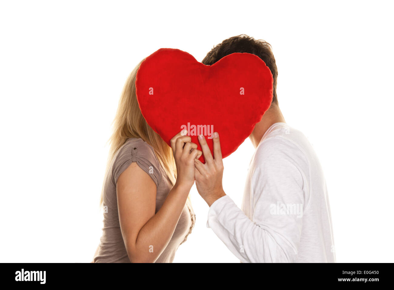Pair in love kisses each other behind a heart. Love is nice. Confidential love, Verliebtes Paar kuesst sich hinter einem Herz. L - Stock Image