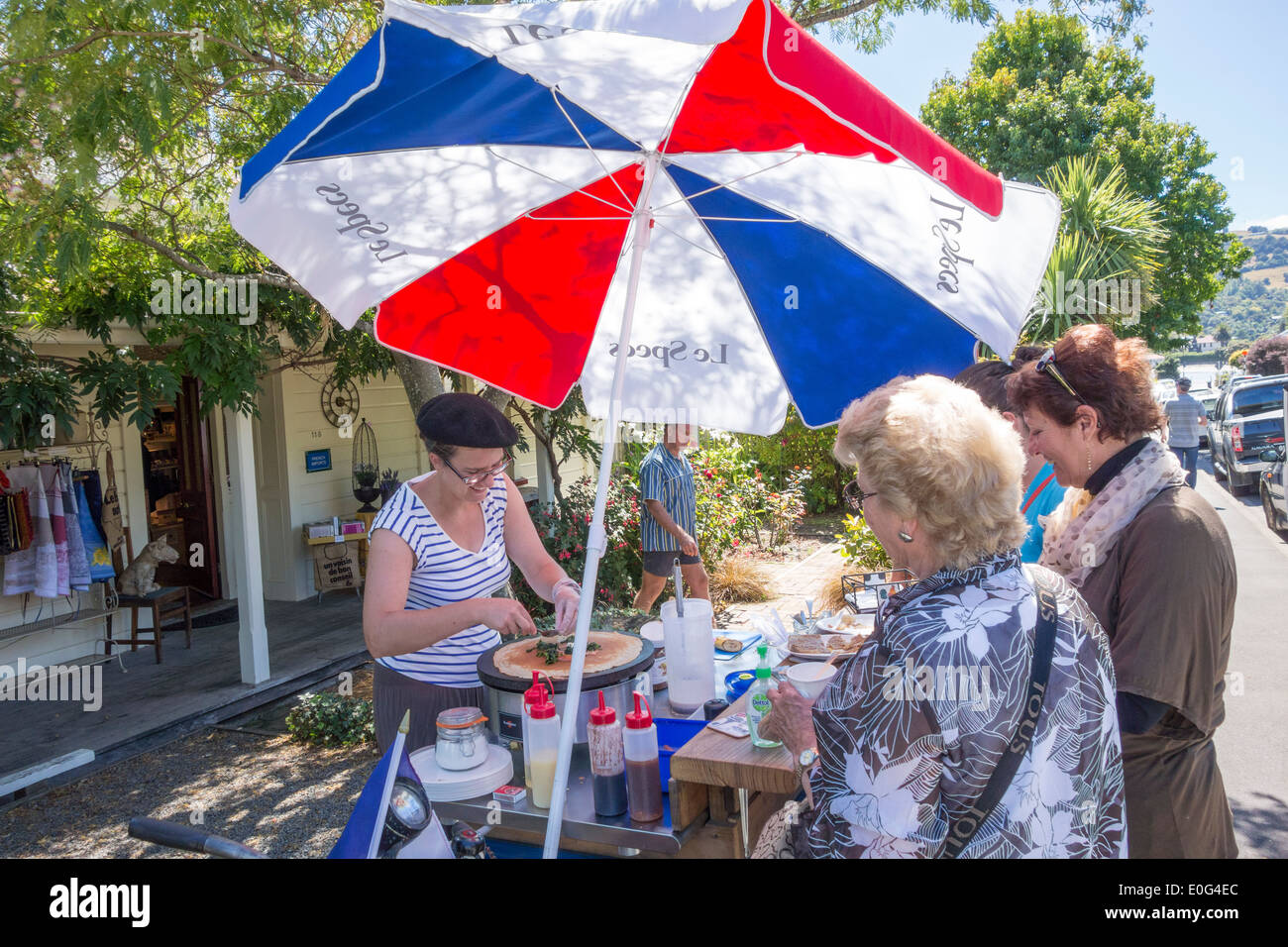 Akaroa New Zealand - Les Crêpes d'Elise making selling French crepes pancakes to cruise passengers from a food cart at French shop La Folie Jolie - Stock Image