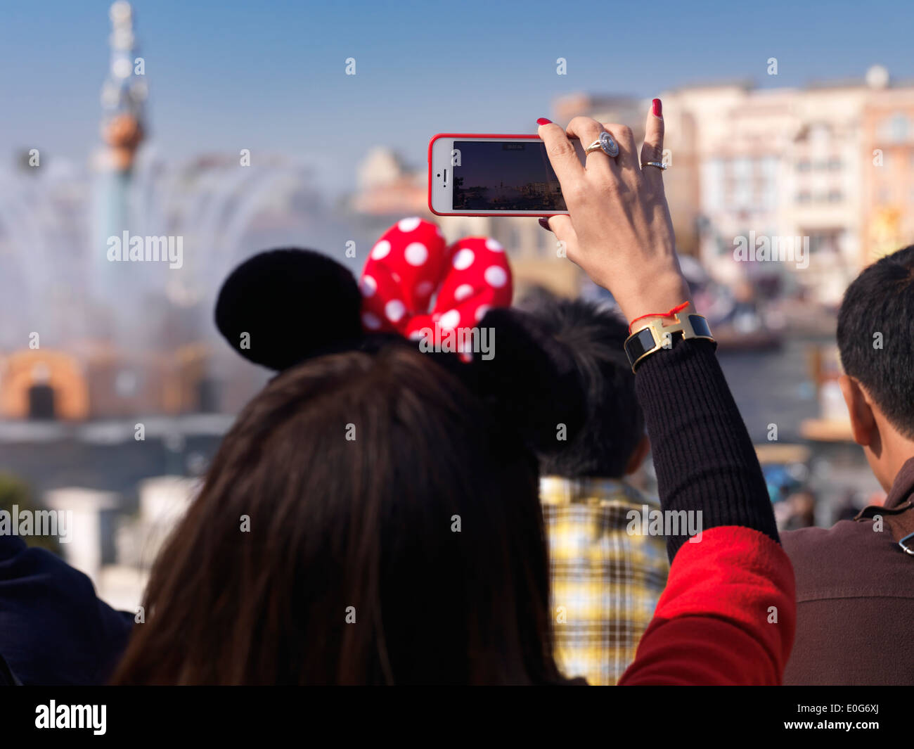 Woman taking pictures with iPhone of a show at Tokyo Disneysea theme park. Japan. Stock Photo
