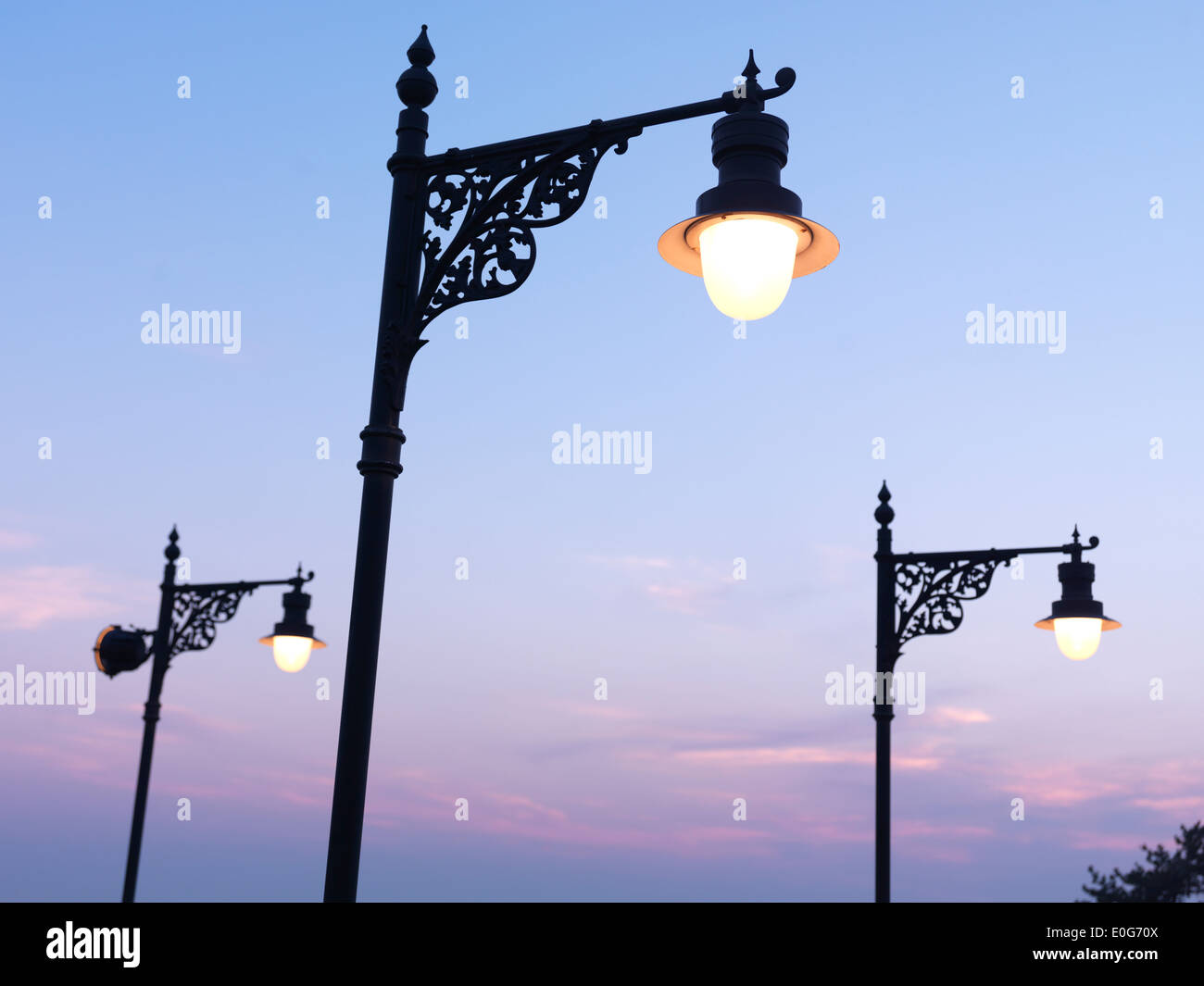 Vintage street lamps over sunset sky background - Stock Image