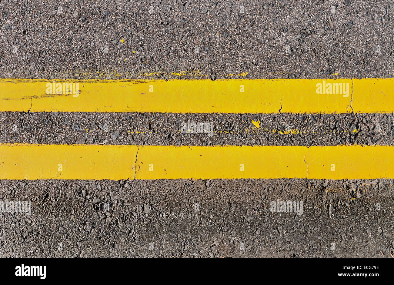 Double yellow lines running horizontally on an asphalt road. - Stock Image