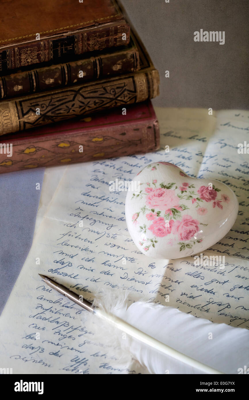 a quill on an old letter with books - Stock Image