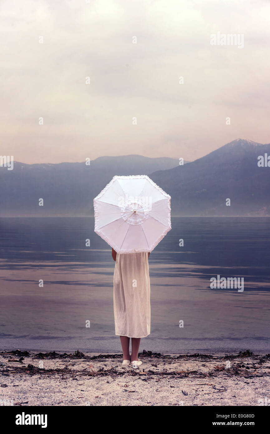 a girl with a parasol at the beach - Stock Image