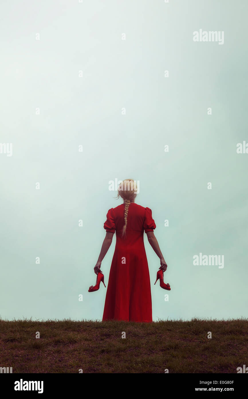 a girl in a red dress on a meadow with her shoes in her hands - Stock Image